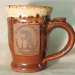 Three color Rendezvous Coffee Mug. Beige, speckled brown, and reddish brown. On the front is the event logo.